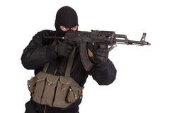 Террорист в черной форме и маска при изолированный автомат Калашниковаа Стоковое фото RF