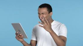 Теряя молодой африканский человек в ударе пока используя планшет, голубую предпосылку