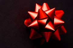 тесемка красного цвета смычка черноты предпосылки стоковое фото