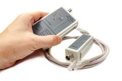 Тестер кабеля сети в руке ` s человека и удаленный зонд с UTP привязывают на белой предпосылке Стоковое фото RF