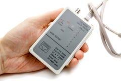 Тестер кабеля сети в руке ` s человека и UTP привязывают на белой предпосылке Стоковое фото RF