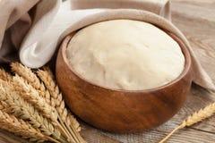 Тесто в деревянном шаре и ушах зрелой пшеницы на старых досках Сельская концепция Стоковые Изображения RF