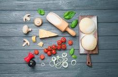 Тесто и ингридиенты для пиццы на деревянной предпосылке, взгляд сверху Стоковые Фото