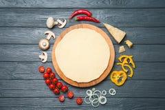 Тесто и ингридиенты для пиццы на деревянной предпосылке, взгляд сверху Стоковая Фотография