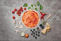 Тесто с соусом и ингридиентами для пиццы на таблице Стоковые Изображения