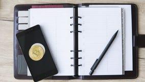 Тетрадь горнорабочей Bitcoin Bitcoins на умных телефоне и ручке на открытой тетради Открытый космос для положил текст на страницы Стоковые Изображения