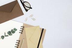 Тетрадь, зрелища, конверты, золотой карандаш, бумажные зажимы, ветвь эвкалипта на белой предпосылке стоковые изображения