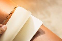 Тетрадь или блокнот руки открытые бумажные на коричневой предпосылке - Vintag Стоковые Изображения RF