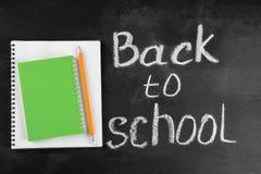 Тетрадь и блокнот с карандашем на предпосылке школьного правления с надписью стоковые фото