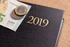 Тетрадь и деньги на таблице Банкноты блокнота и евро Концепция планирования бизнеса, перемещения, домашних расходов стоковое изображение
