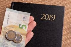 Тетрадь и деньги на таблице Банкноты блокнота и евро Концепция планирования бизнеса, перемещения, домашних расходов стоковое фото rf
