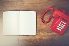 Тетрадь и красный телефон Стоковые Изображения