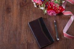 Тетрадь и ручка лежали на коричневой деревянной предпосылке Пук цветка и cornflower мака стоковые изображения