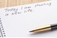 Тетрадь и ручка рабочего места взгляда сверху на деревянной предпосылке таблицы Надпись - сегодня я начинаю новая жизнь стоковая фотография
