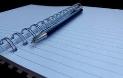 Тетрадь и черная ручка стоковое изображение