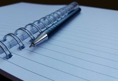 Тетрадь и черная ручка стоковое фото