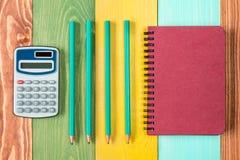 Тетрадь, калькулятор и 4 карандаша Стоковые Фото