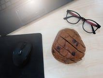 Тетрадь, коврик для мыши, мышь, стекла и хлеб reisins помещенный дальше Стоковые Фотографии RF