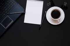 Тетрадь, компьтер-книжка, ручка и кофе на столе офиса Стоковые Фото