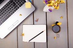 Тетрадь, кофе и цветки для женских дома или рабочего места офиса на деревянной предпосылке Взгляд сверху скопируйте космос Стоковые Изображения