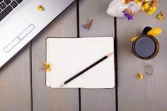 Тетрадь, кофе и цветки для женских дома или рабочего места офиса на деревянной предпосылке Взгляд сверху скопируйте космос Стоковая Фотография