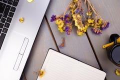 Тетрадь, кофе и цветки для женских дома или рабочего места офиса на деревянной предпосылке Взгляд сверху скопируйте космос Стоковое Фото