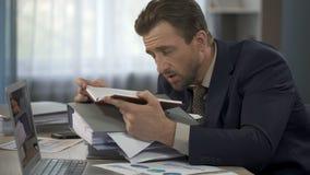 Тетрадь отверстия менеджера, чтение для того чтобы сделать список, кладя голову на кучу бумаг, утомляла сток-видео