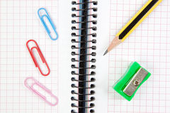 Тетрадь, пер, точилка для карандашей и зажим. Стоковые Фото