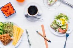 Тетрадь планирования взгляд сверху с космосом экземпляра и здоровый сандвич завтрака с яичком Венедиктом и копчеными семгами, пли Стоковая Фотография