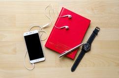 Тетрадь пробела крышки Красной книги с ручкой на деревянной таблице и чае телефона шлемофона наручных часов современном Стоковые Фото