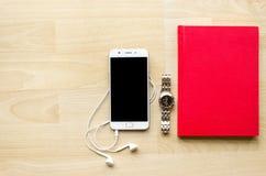 Тетрадь пробела крышки Красной книги с ручкой на деревянной таблице и чае телефона шлемофона наручных часов современном Стоковое Фото