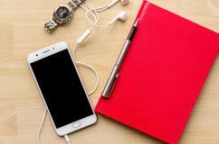 Тетрадь пробела крышки Красной книги с ручкой на деревянной таблице и чае телефона шлемофона наручных часов современном Стоковое Изображение RF