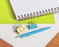 Тетрадь, ручка, и зажимы для бумаги на таблице отделывают поверхность Стоковое Изображение