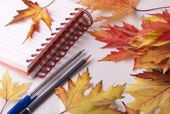 Тетрадь, ручка, карандаш и листья Стоковые Фотографии RF