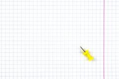 Тетрадь студента в клетке с красной линией Лист лежит желтый pushpin стоковое изображение rf