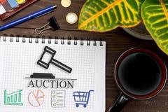 Тетрадь с аукционы примечаний онлайн на таблице офиса с Стоковое фото RF