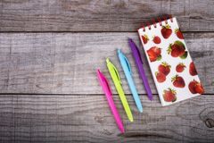 Тетрадь с клубниками и набором покрашенных ручек на деревянной предпосылке стоковые изображения