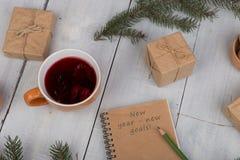тетрадь с текстом ' Новый Год - новое goals' , карандаш, подарочные коробки, гайки, ветви ели и чашка чаю стоковое фото rf