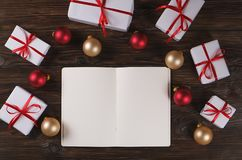 Тетрадь с украшением рождества и подарки на деревянной предпосылке Сделать список, концепция письма santa Взгляд сверху, плоское  Стоковые Изображения