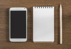 Тетрадь, smartphone и карандаш на древесине скопируйте космос Стоковая Фотография RF