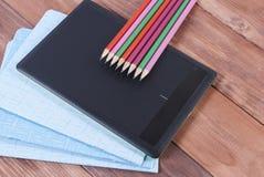 Тетради с прописями, карандаши, и таблетка на деревянной поверхности стоковое изображение rf