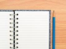 Тетрадь взгляд сверху пустая и голубой карандаш Стоковые Изображения