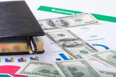Тетрадь лежит на графиках течения и долларах Стоковые Изображения RF