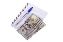 Тетрадь, деньги, ручка на белой предпосылке Стоковое Изображение