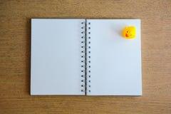 Тетрадь и желтая утка на деревянном столе Стоковые Фото