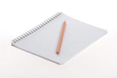 Тетрадь и карандаш на белой предпосылке Стоковые Изображения