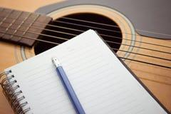 Тетрадь и карандаш на гитаре Стоковое Фото