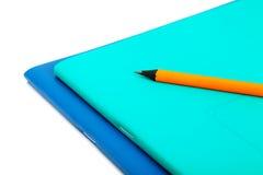 Тетрадь и карандаш 2 общих на белизне Стоковое фото RF