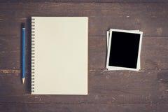 Тетрадь и карандаш с фото рамки на деревянных wi предпосылки таблицы Стоковое фото RF