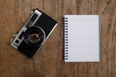 Тетрадь и классика камеры на деревянном Стоковые Фото
